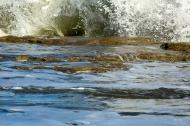 photo of wave breaking on rocks.