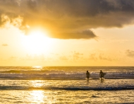 photo of Sufers entering water at Sunrise